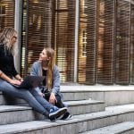 Two women sitting on steps and talking